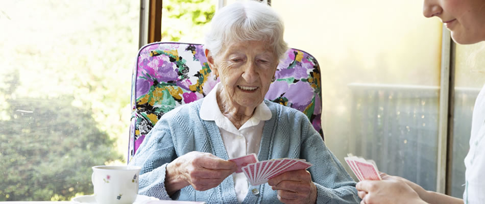 Older woman plays card